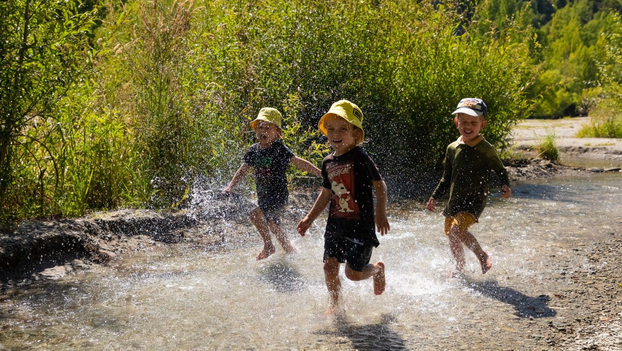 Children enjoying water play in the Bush Creek/Arrow River on Arrowtown's outskirts